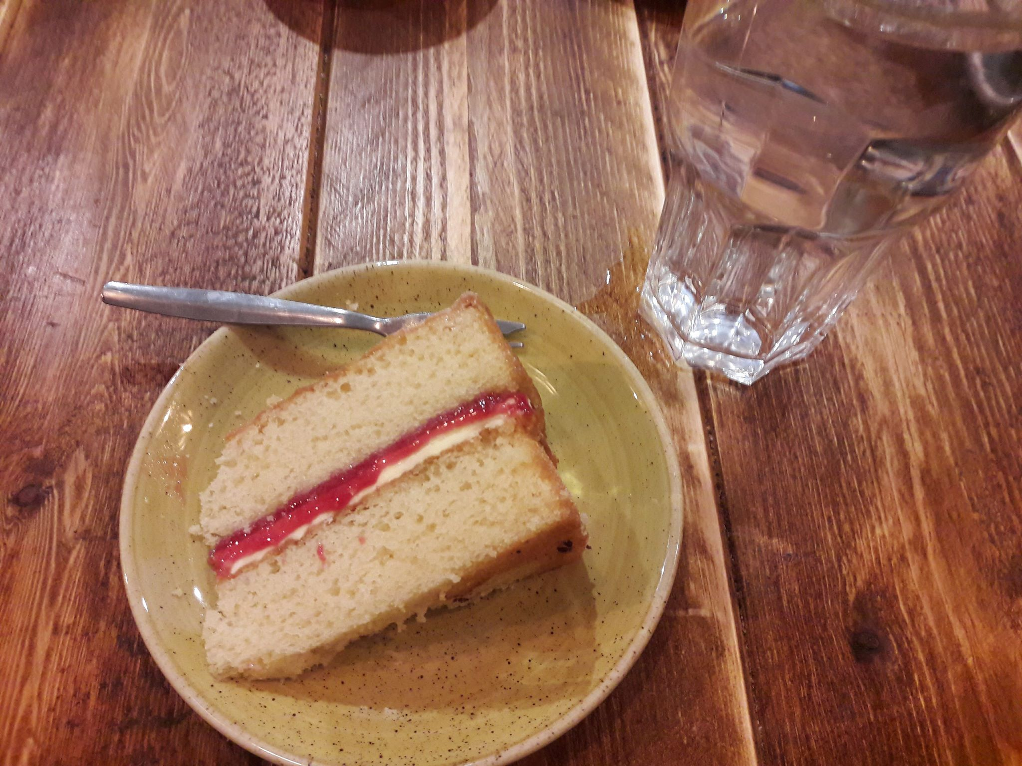 Image of a slice of Victoria sponge cake on a small plate and a glass of water, both on a wooden table