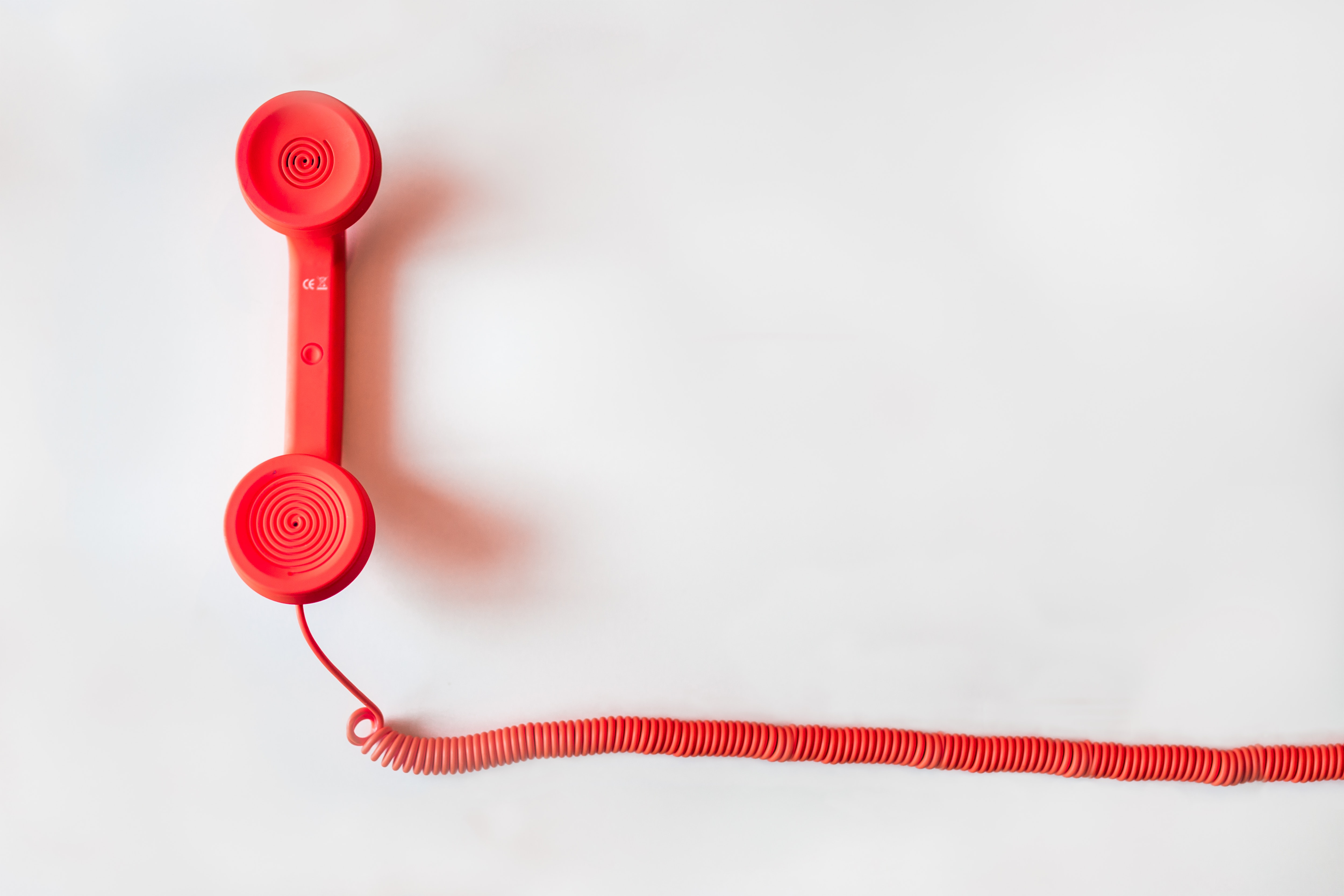 Stock photo of a red telephone with a red telephone wire on a plain white background.