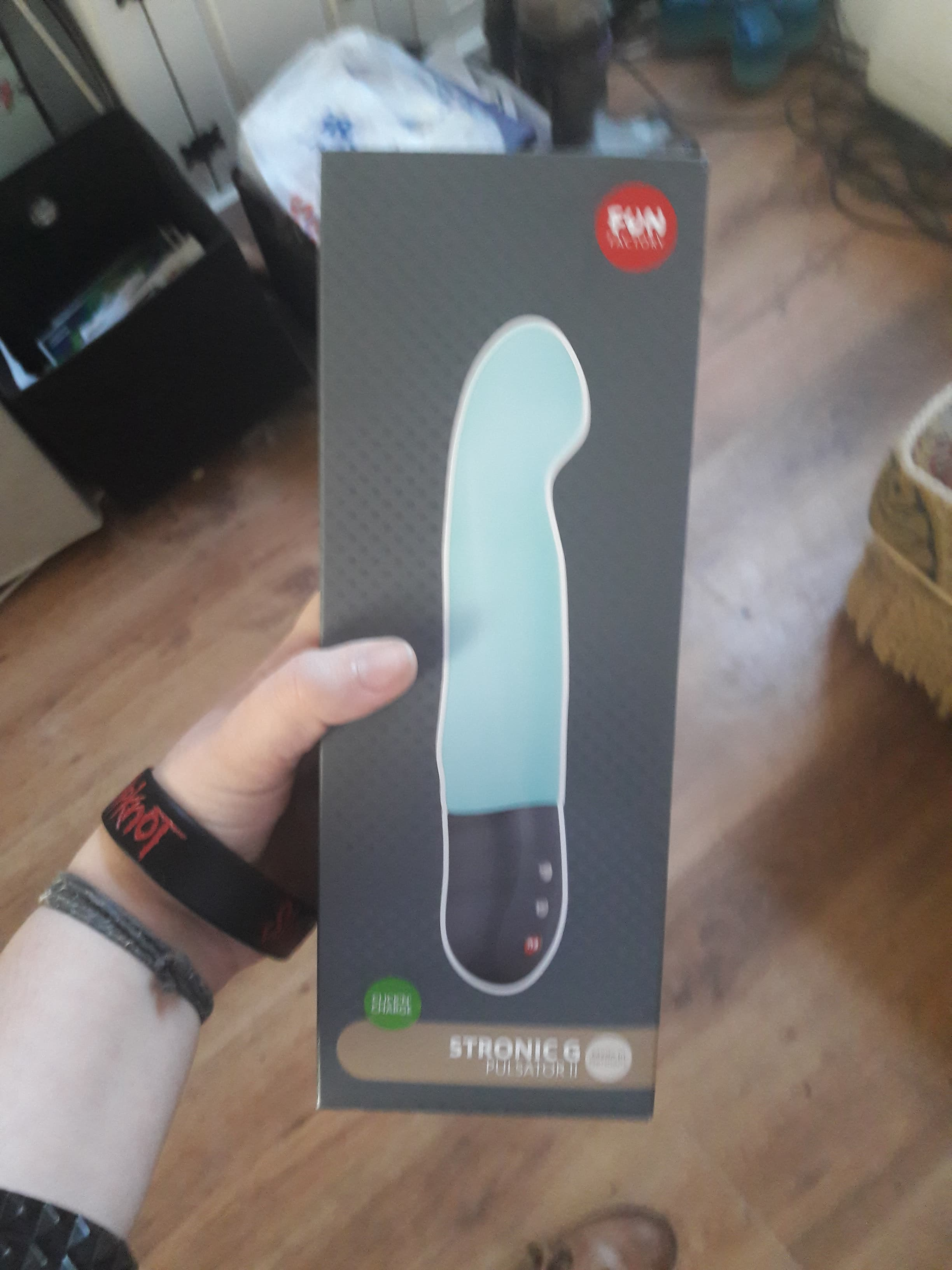 Image is of a white hand (Morgan's) holding a box with a picture of the blue Fun Factory Stronic self-thrusting dildo on it.