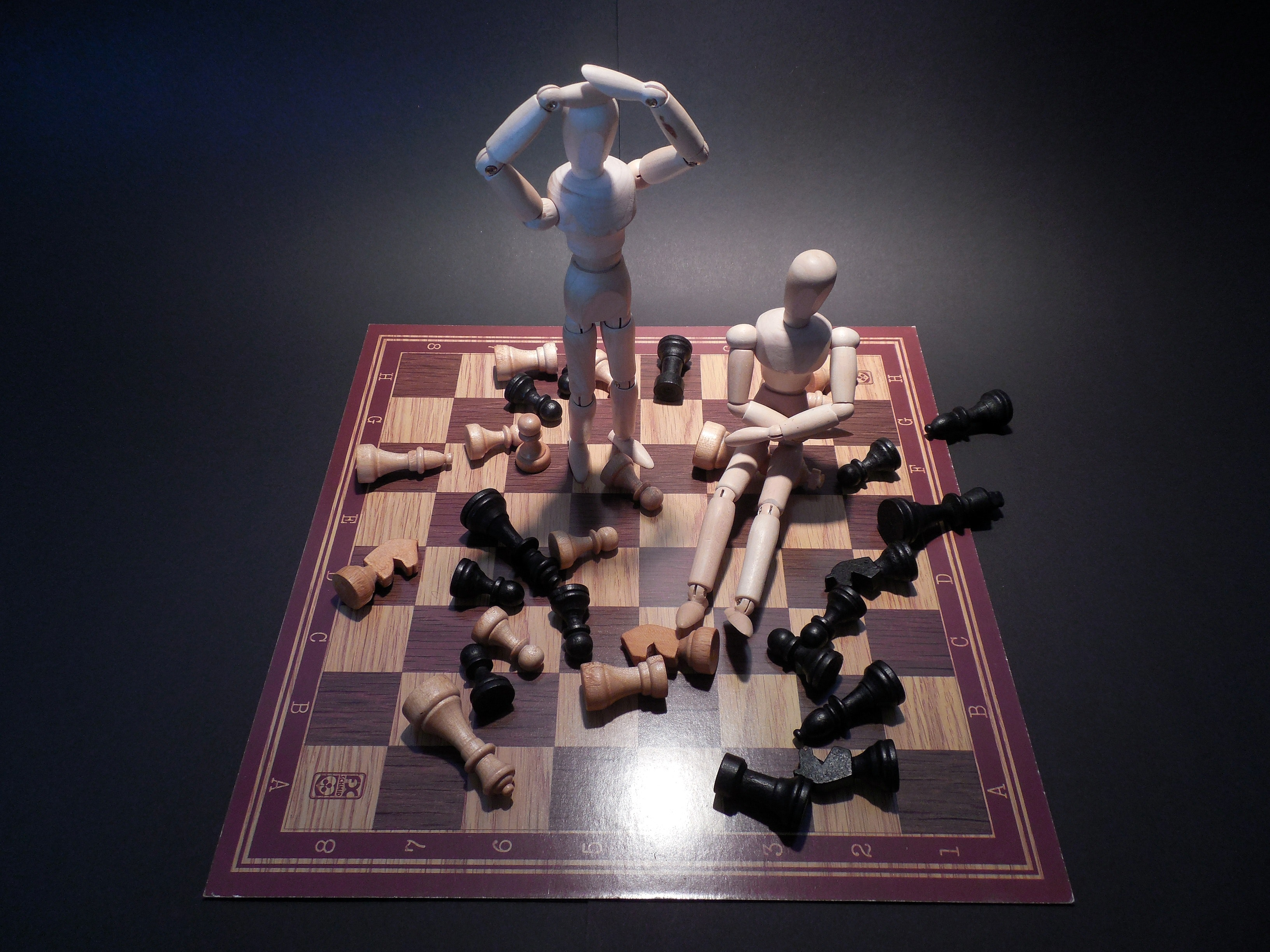 A stock photo depicting two wooden artists' mannequins on a chess board, one seated and one standing. The mannequin who is standing has its hands on its head in dismay and the chess pieces are scattered haphazardly around them both, representing autistic meltdowns in an adult. The background is black, like my soul after dealing with neurotypical douchebags.