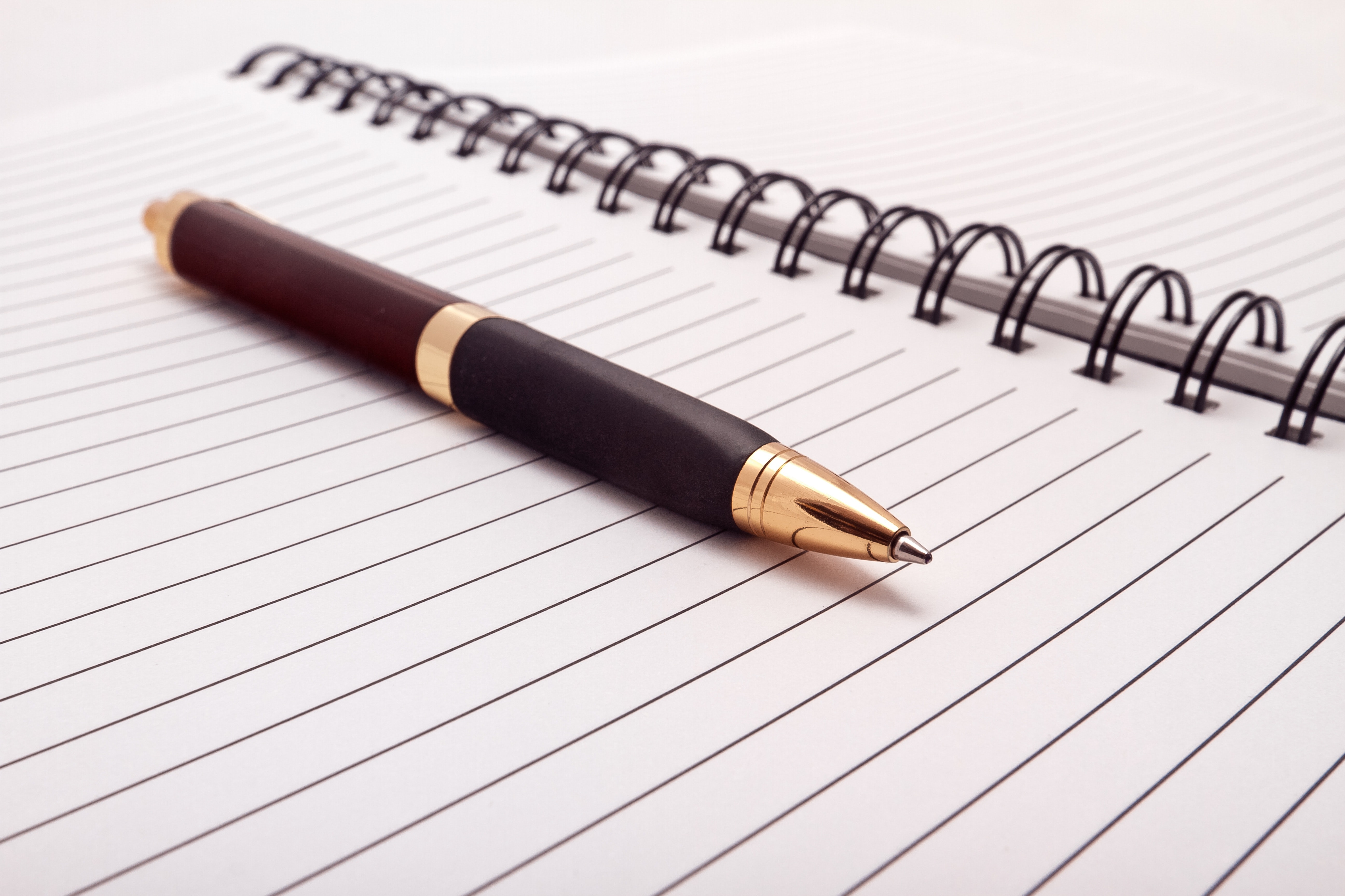 Stock photo of a blank, lined, spiral-bound notebook, open and with a fancy pen sitting on top of it