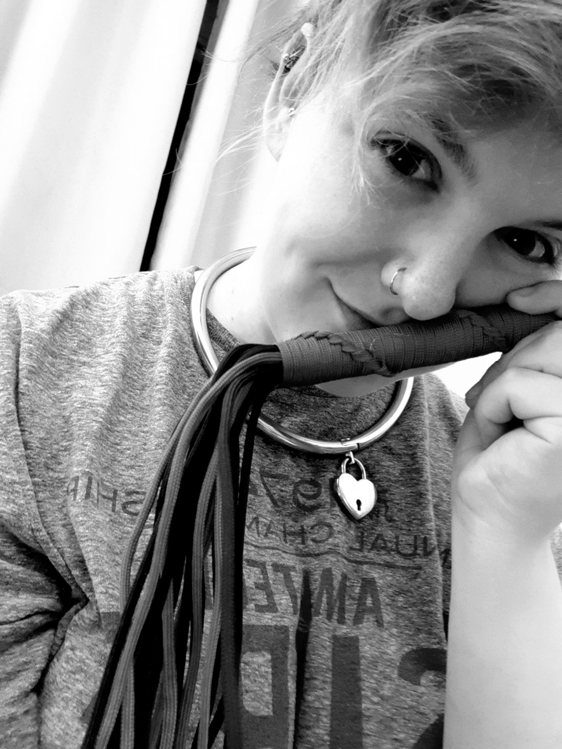 Greyscale photo of Morgan, a white nonbinary human with piercings, holding a mini flogger and smirking at the camera to suggest they're in topspace