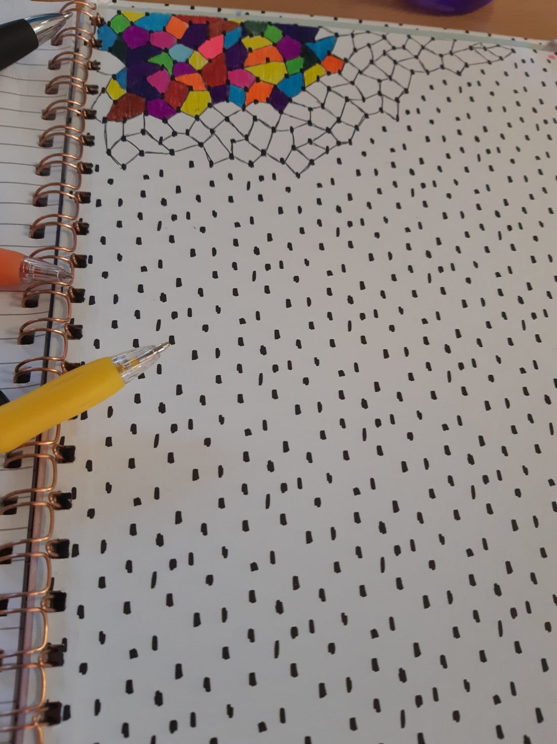 A photo of Morgan's notebook, which xe has begun to colour in with an irregular pattern, using biro