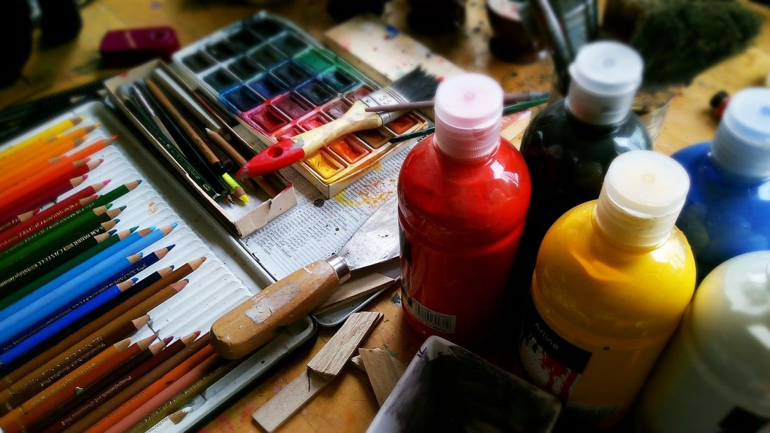 A stock photo of paints, pencils, etc on a messy desk, cause you know, every artist is a hot mess
