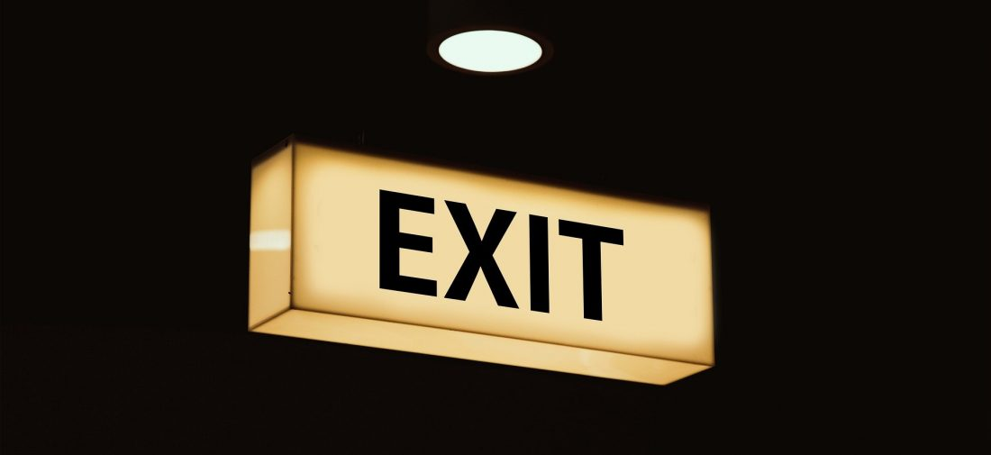 An exit sign, lit up against a dark background